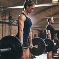 Female and male athletes performing deadlifts at a CrossFit gym