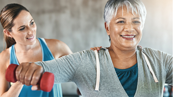 older female adult lifting weights with physical therapist assistance