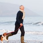older male adult running with his dog on a beach