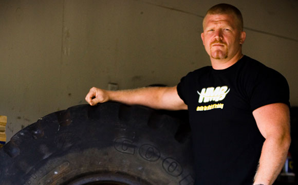 Strongman athlete Eric Todd posing with tire implement