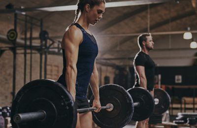 female and male athlete deadlifting during CrossFit workout