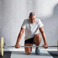 older male adult weight lifting barbell