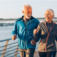 two older adults running along the water