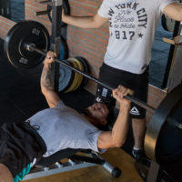 male athlete bench pressing in a gym / myHMB blog build a bigger bench press with the floor press