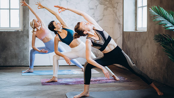 three woman in yoga studio doing extended triangle pose / myhmb helps improve body composition