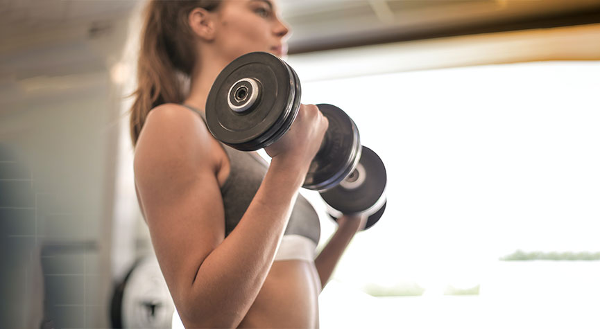 woman in a gym doing bicep curls with dumbbells