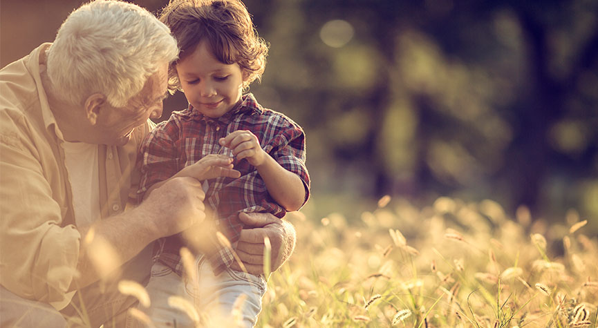 grandfather arm wrapped around his grandson in a field during a sunny day