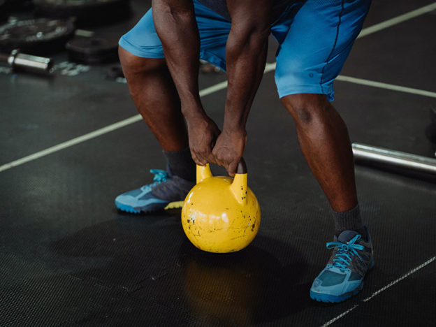 man in a gym lifting a yellow kettbell off the floor / myHMB blog Fitness Gear Must-Haves by Jennifer Dietrick