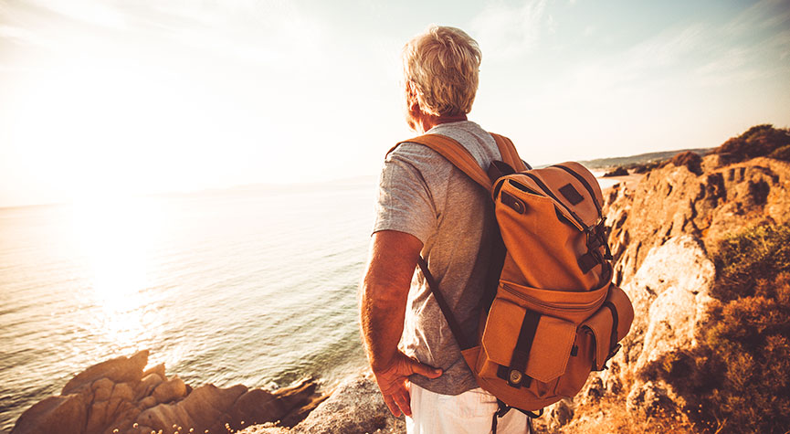 older male with orange backpack hiking next to the ocean