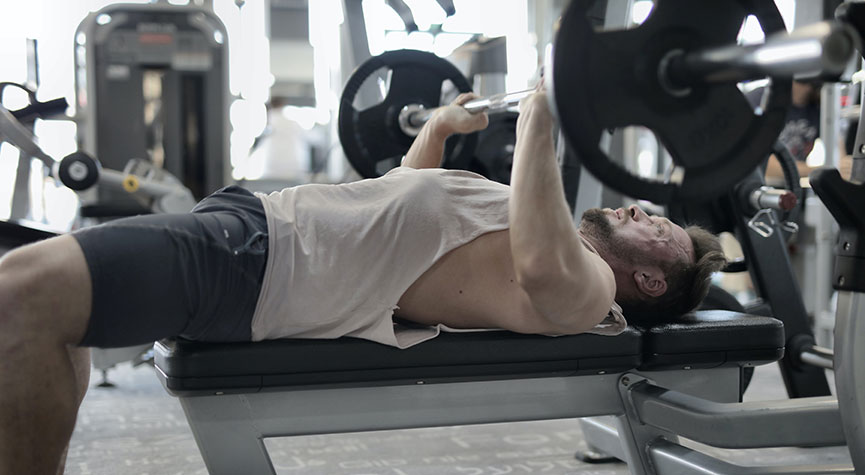 man in a gym performing the bench press