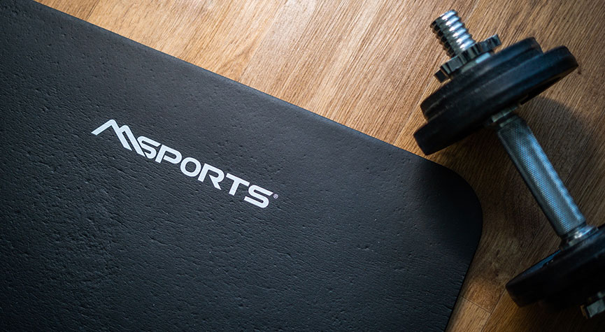 wooden floor with a msports gym mat and one dumbbell