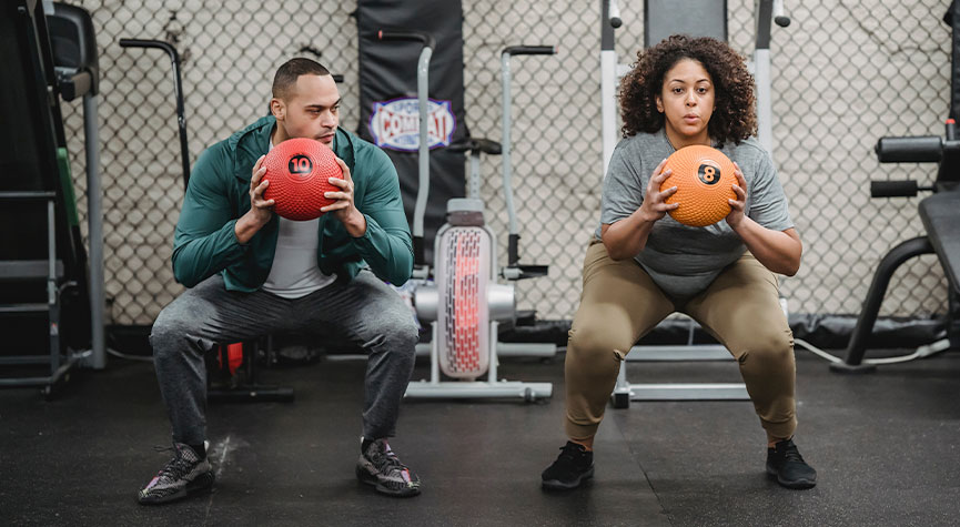 personal male trainer and female performing medicine ball squats