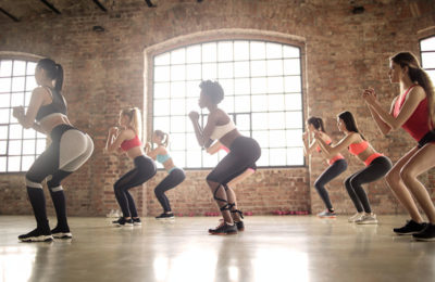 women in a fitness group class all performing a bodyweight squat / myHMB Blog back to the basics - the squat by Carissa Johnson