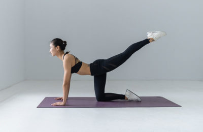woman on a yoga mat in a studio stretching her leg back into the air
