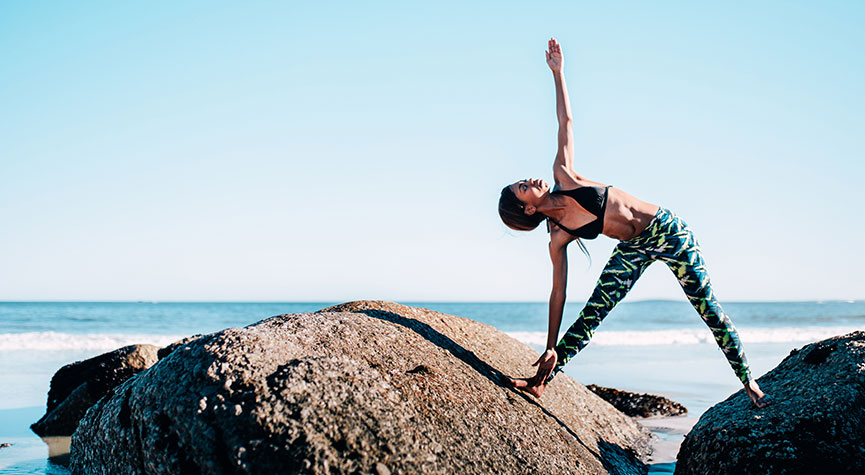 woman doing yoga on the rocks in front of the ocean